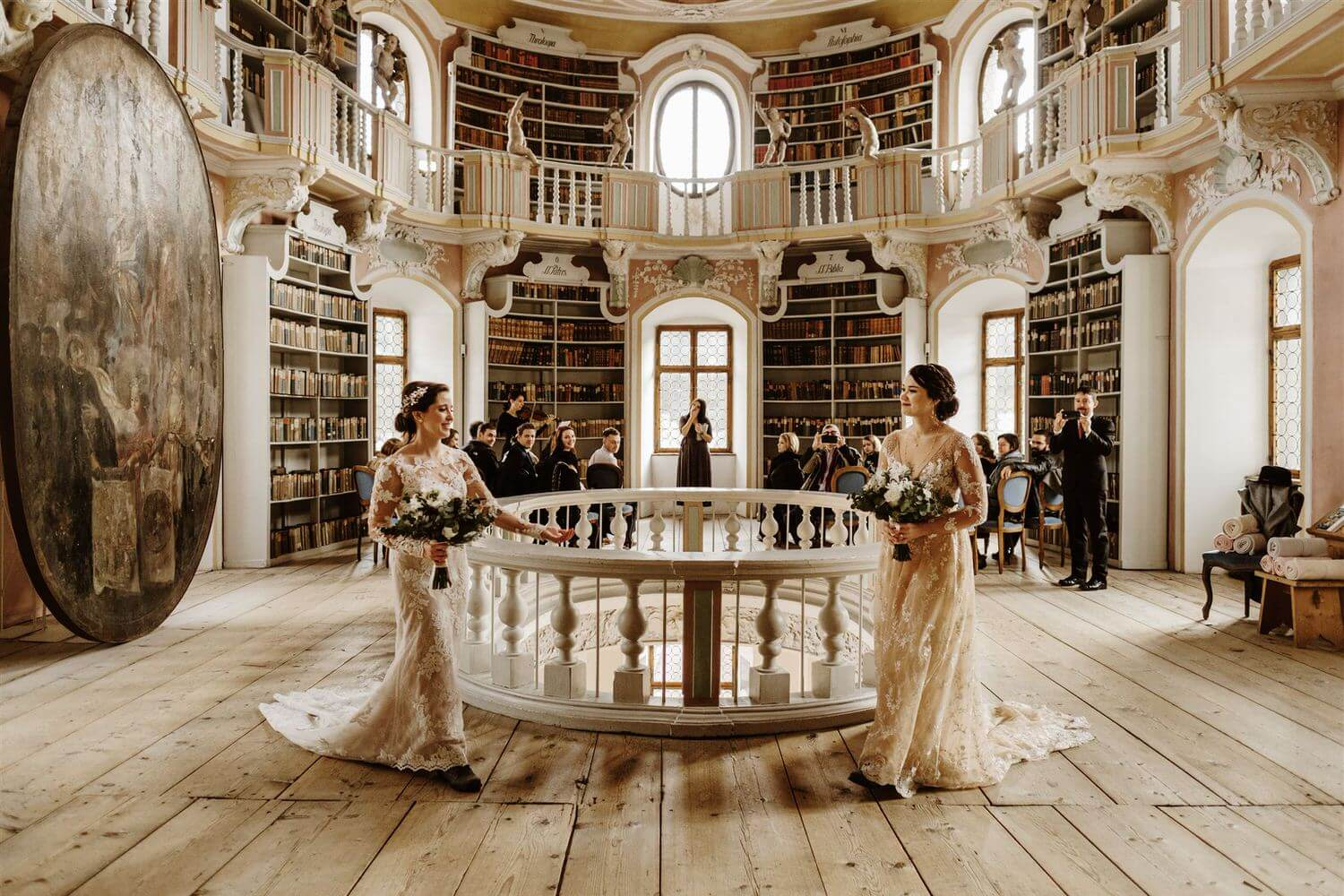 Two brides walk towards each other after their wedding ceremony in a library