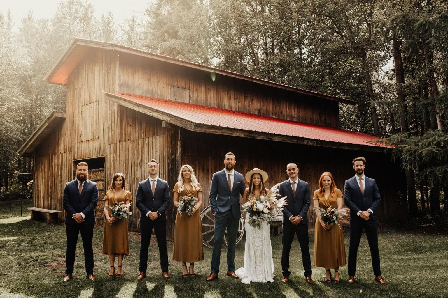 Wedding Party standing in front of a Red Barn during the fall