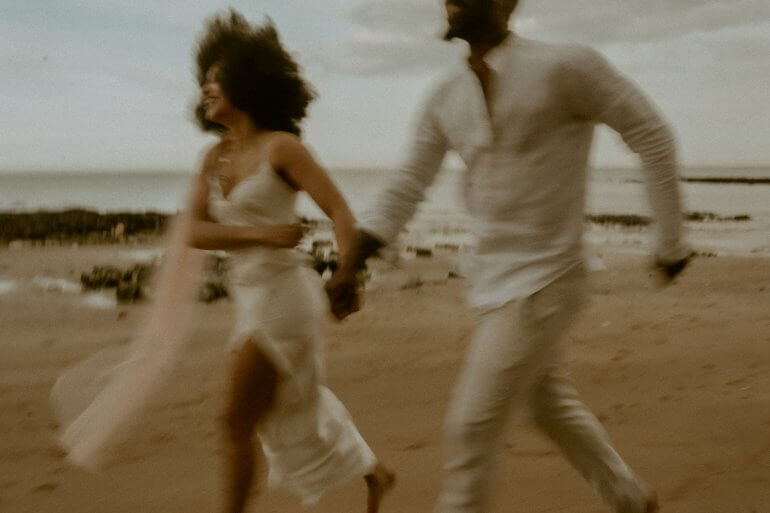 Two people running, on the beach, blurred motion